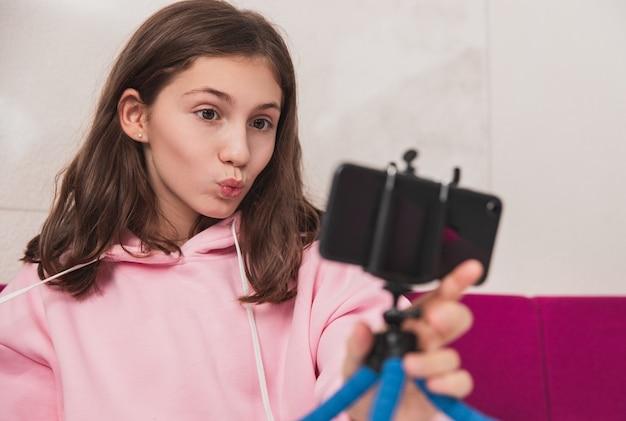 Meisje in trendy hoodie lippen pruilen en het nemen van selfie met smartphone zittend op de bank