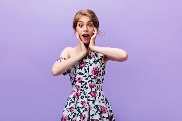 Meisje in trendy jurk kijkt verbaasd. geschokt jonge vrouw met roze lippen in modieuze lichte kleding die zich voordeed op geïsoleerde achtergrond.