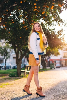 Meisje in trendy kleding met lang haar kijkt naar camera en glimlach. stadsstraat en sinaasappelbomen.