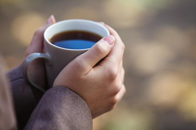 Meisje in trui met een kopje koffie