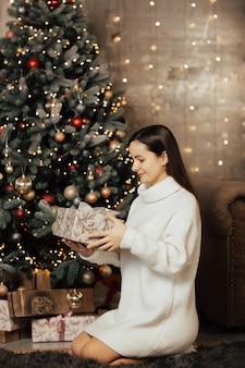 Meisje in trui zit in de buurt van de kerstboom en houdt een kerstcadeautje.