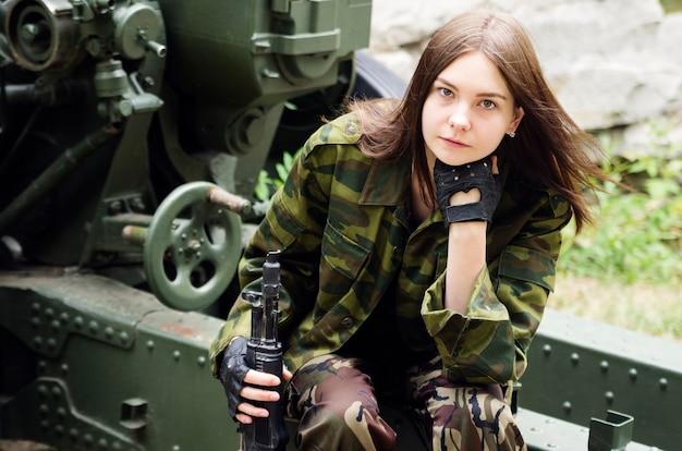 Meisje in uniform met een machinepistool zittend op een artilleriekanon