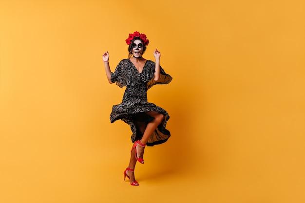 Meisje in v-vormige jurk danst en heeft plezier. vrouw in afbeelding van skelet heeft plezier voor een foto van volledige lengte