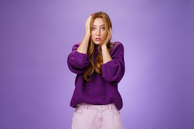 Meisje in verdoving voelt zich geschokt en verontrust omdat ze zich realiseert dat ze een grote fout heeft gemaakt, handen op het gezicht houdt en ogen naar de camera kijkt, verward en hopeloos, angstig poserend over paarse achtergrond.