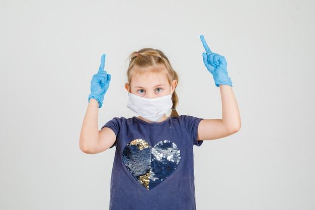 Meisje in vingers t-shirt, handschoenen en masker omhoog wijzen en voorzichtig kijken. vooraanzicht.