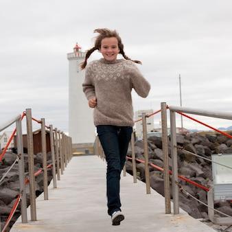 Meisje in vlechten rennen geschokte loopbrug van vuurtoren