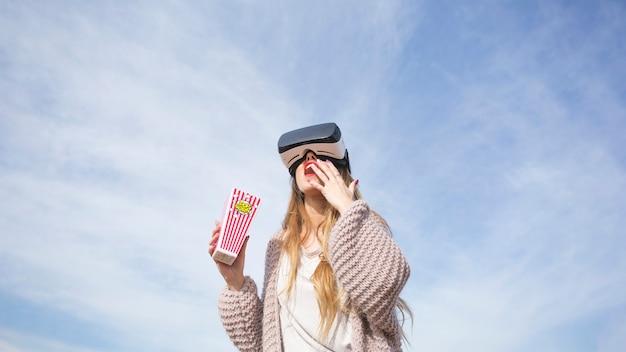 Meisje in vr-hoofdtelefoon met popcorn