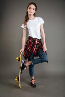 Meisje in vrijetijdskleding die en skateboard bevinden zich houden