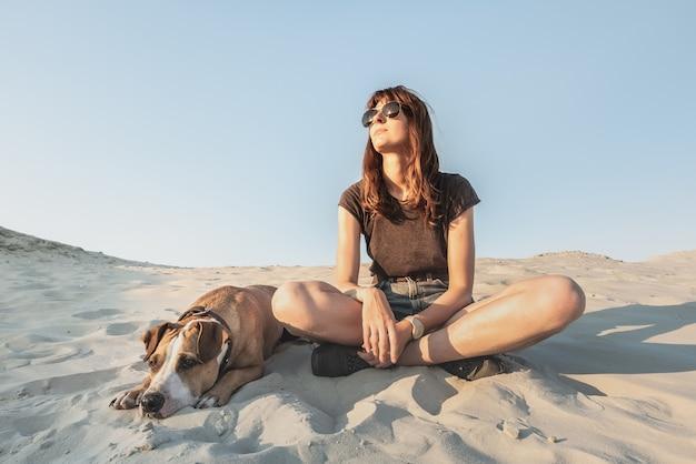 Meisje in vrijetijdskleding wandelen en staffordshireterriër puppy genieten van warme zomerdag. mooie jonge vrouw in zonnebril berust met hond op zandstrand of woestijn.