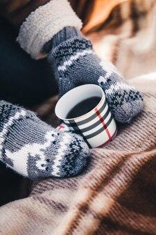 Meisje in wanten houdt een kopje met een warme drank op de plaid in de winter
