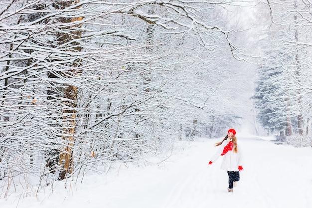 Meisje in warme kleren rennen en glimlachen in een winterpark tussen de sneeuw