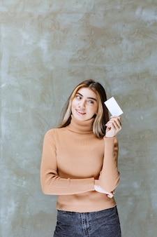 Meisje in warme trui die haar visitekaartje presenteert