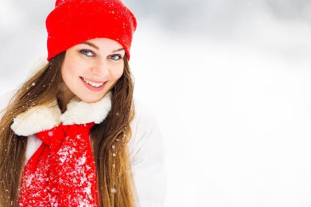 Meisje in winterjas en rode hoed met sjaal glimlacht en kijkt naar de camera
