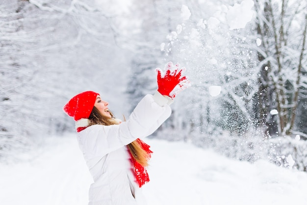 Meisje in winterkleren gooit sneeuw in park