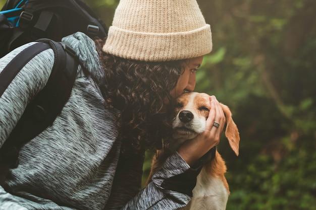 Meisje in winterkleren in de natuur die haar hond kust terwijl hij zijn ogen sluit.
