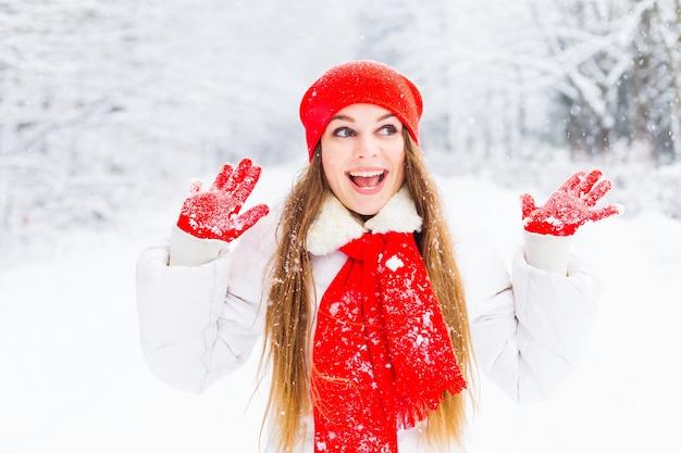 Meisje in wit de winterjasje en rode hoed met sjaal en handschoenen