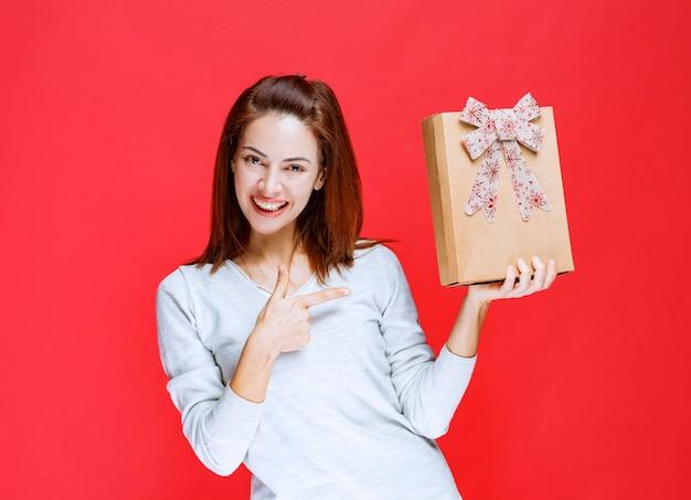 Meisje in wit overhemd dat een kartonnen geschenkdoos vasthoudt en een positief handteken toont