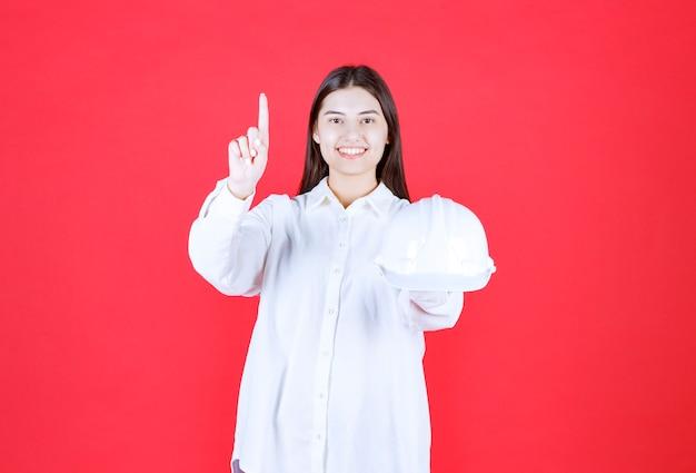 Meisje in wit overhemd dat een witte helm vasthoudt en ergens naar wijst