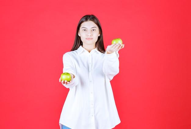 Meisje in wit overhemd dat groene appels in de hand houdt en aan de klant aanbiedt