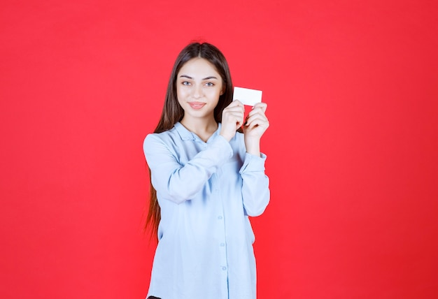 Meisje in wit overhemd dat haar visitekaartje voorstelt.