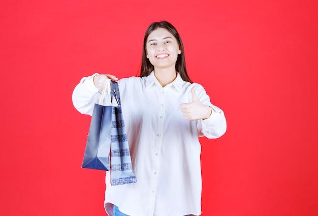 Meisje in wit overhemd dat meerdere boodschappentassen vasthoudt en een positief handteken toont