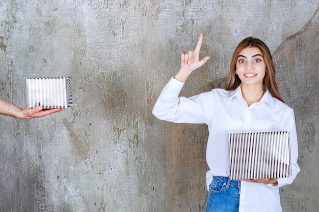 Meisje in wit overhemd dat op een betonnen muur staat, krijgt een zilveren geschenkdoos aangeboden en heeft een goed idee.