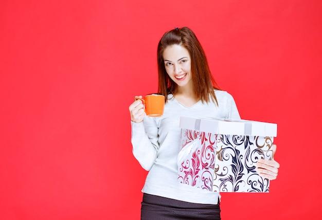 Meisje in wit overhemd met een bedrukte geschenkdoos en een kopje drinken