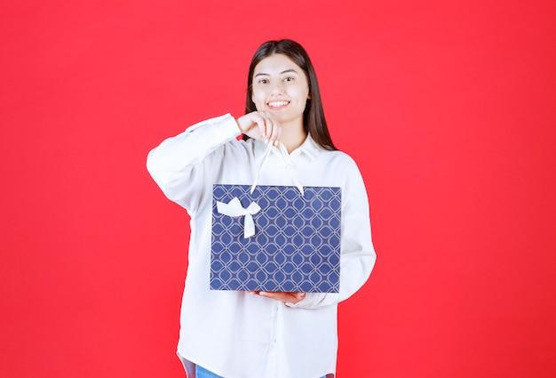 Meisje in wit overhemd met een blauwe boodschappentas