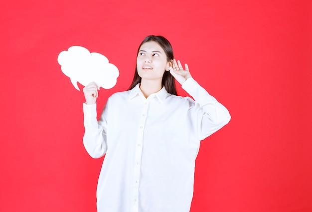 Meisje in wit overhemd met een infobord in de vorm van een wolk en ziet er verward en bedachtzaam uit