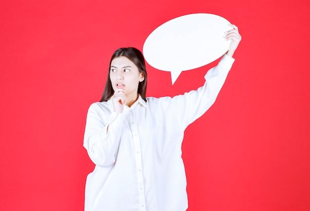 Meisje in wit overhemd met een ovaal infobord en ziet er verward en bedachtzaam uit