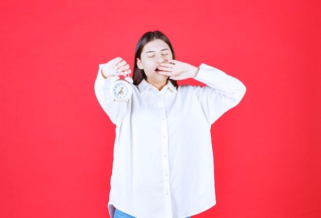 Meisje in wit overhemd met een wekker en ziet er slaperig uit