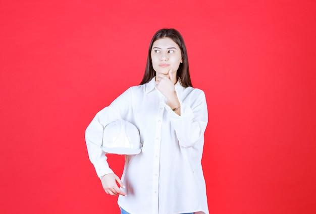 Meisje in wit overhemd met een witte helm en ziet er verward en bedachtzaam uit