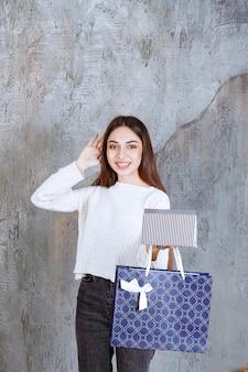 Meisje in wit overhemd met een zilveren geschenkdoos en een blauwe boodschappentas en kijkt verward en nadenkend over het maken van een keuze.