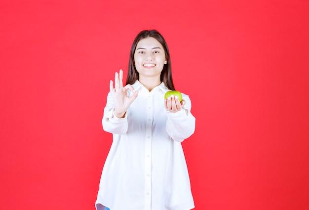 Meisje in wit overhemd met groene appels en genietend van de smaak