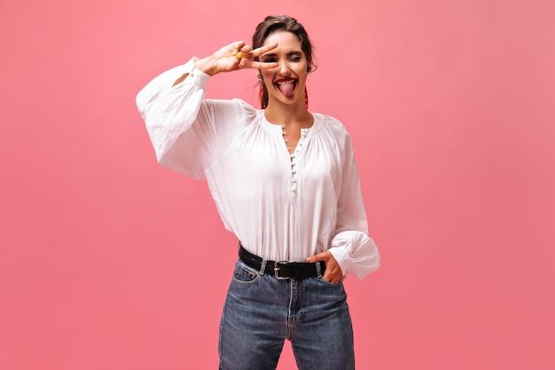 Meisje in witte blouse en jeans die tong en vredesteken tonen. grappige jonge vrouw in stijlvolle kleding die zich voordeed op roze achtergrond.
