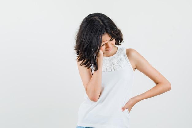 Meisje in witte blouse met hoofdpijn en op zoek boos, vooraanzicht.