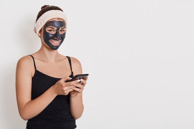 Meisje in witte haarband op haar hoofd en in klei zwart gezichtsmasker houdt mobiele telefoon en schrijft bericht of leest nieuws, doet schoonheidsbehandelingen thuis, gezichtshuidverzorging.