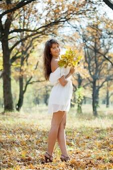 Meisje in witte jurk in de herfstpark