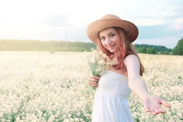 Meisje in witte jurk in het veld met gele bloemen in bloei