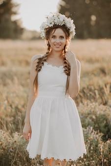 Meisje in witte jurk met bloemen krans en vlechten in zomer veld