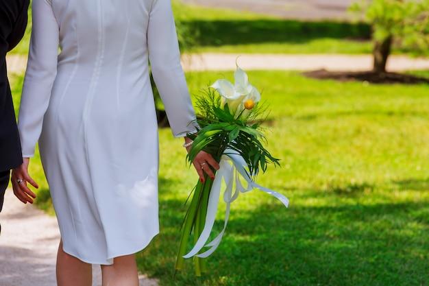 Meisje in witte jurk met een boeket bloemen en groen tegen