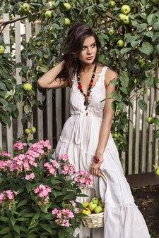 Meisje in witte jurk met fruitmand in de buurt van de boom met appels bloemen in de dorpstuin