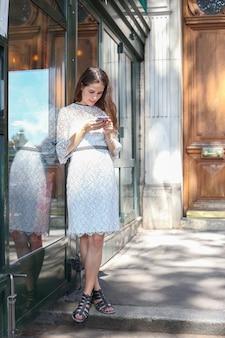 Meisje in witte jurk staat met telefoon in de buurt van glazen vitrine brunette schrijft berichten op de telefoon