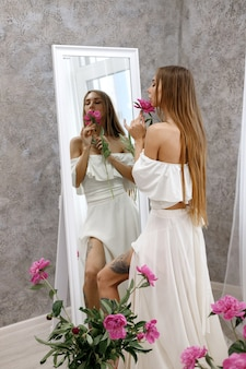 Meisje in witte jurk voor de spiegel met pioenrozen
