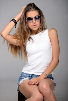 Meisje in witte t-shirt en zonnebril zit en poseert voor de camera.