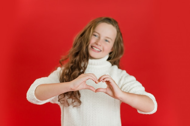 Meisje in witte trui doet een hart met haar handen