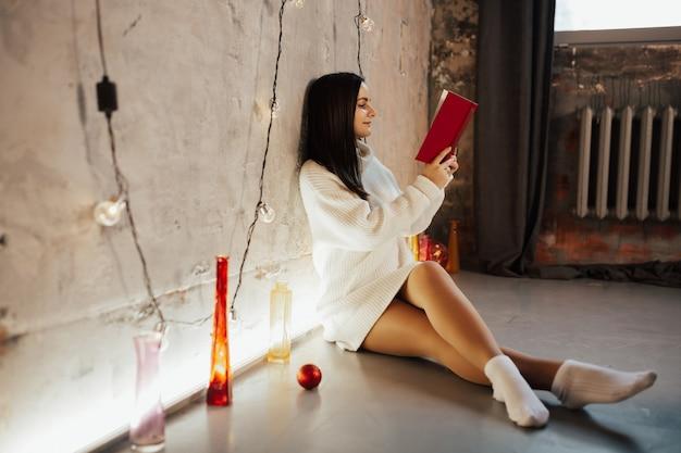 Meisje in witte trui zit op de vloer en leest een boek in een loft-interieur.