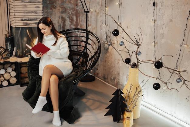 Meisje in witte trui zittend op de fauteuil en lees het boek in een stijlvol interieur van woonkamer met open haard.