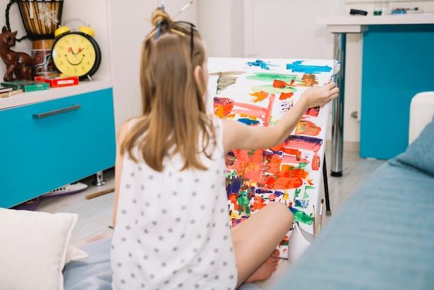 Meisje in witte zitting op vloer en het schilderen met gouache op canvas
