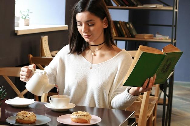 Meisje in zittend aan tafel in cafe gieten thee en een boek te houden